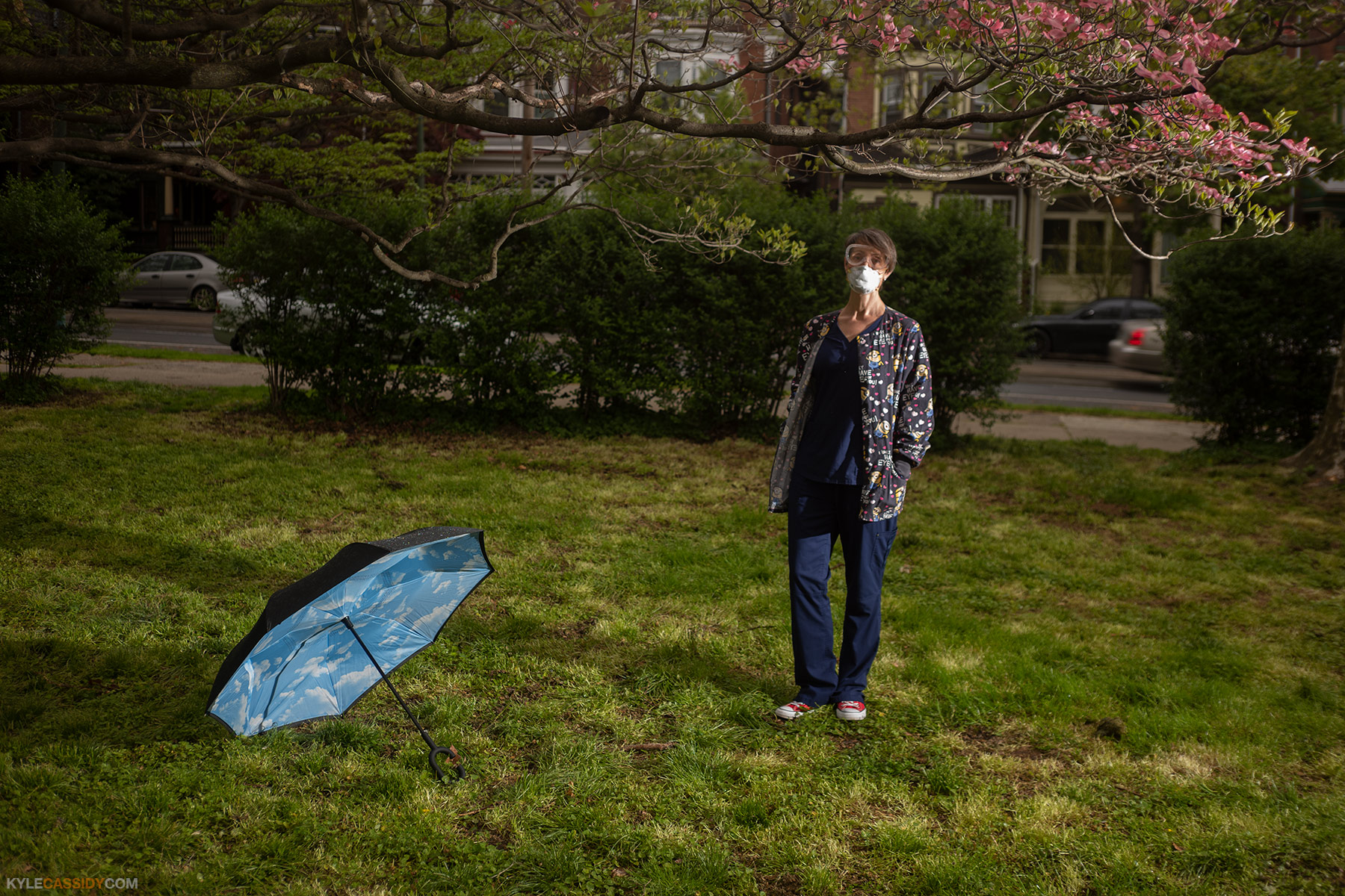 Karen wearing hospital scrubs standing in a park with an open umbrella on the ground next to her. She is wearing a surgical mask.