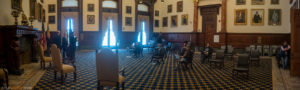 A large room in city hall with very few people in it, spread out in chairs 15 feet apart.