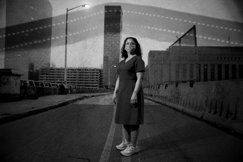 A nurse, in black and white, standing in the middle of an empty bridge in the very early morning. She's wearing a handmade mask.