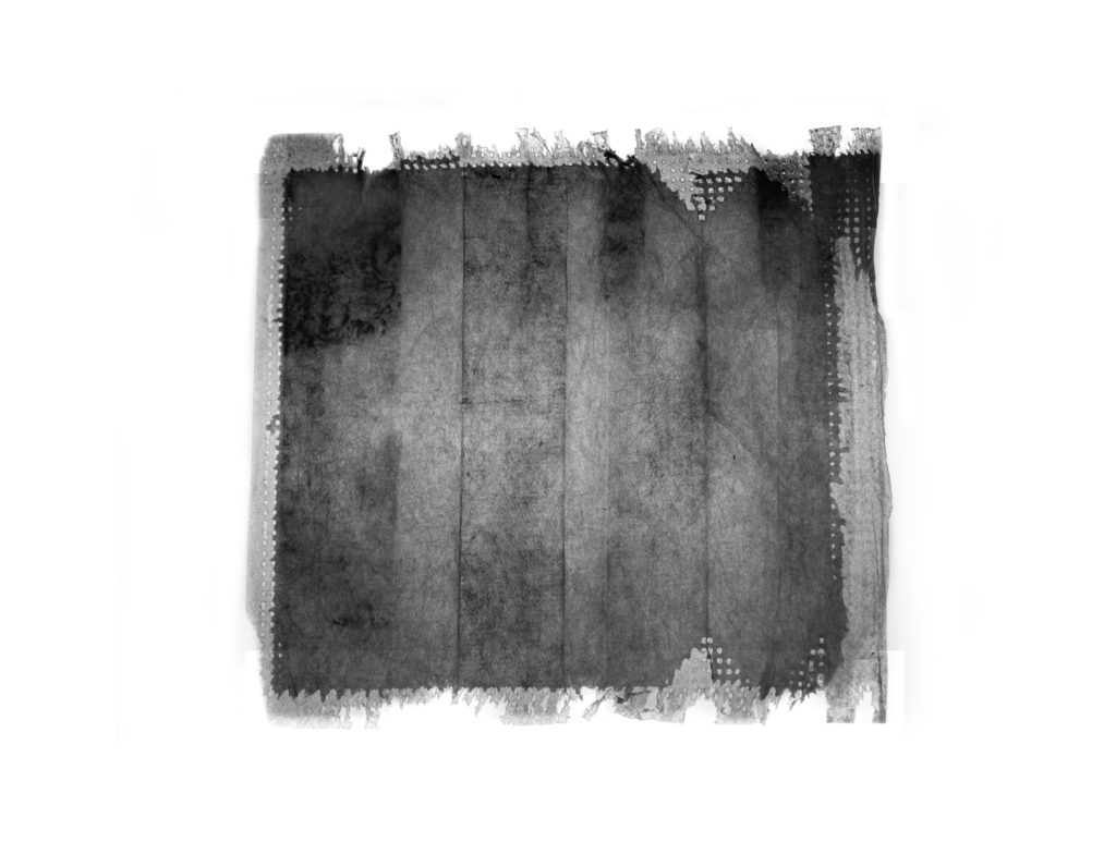 A black and white image of a torn layer of a surgical mask.